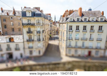 Street view on the beautiful residential buildings andchurch tower in Nantes city during the sunny day in France. Tilt shift image technic