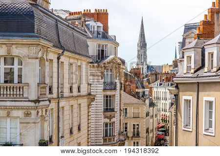 Street view on the beautiful residential buildings andchurch tower in Nantes city during the sunny day in France