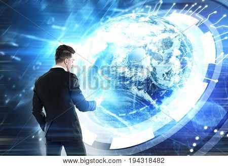 Young businessman holding a smartphone and standing against a futuristic background with a giant Earth hologram. Mock up toned image.
