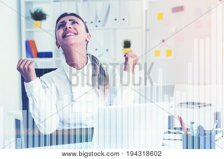 Close up portrait of a black haired businesswoman wearing a white shirt and sitting at her table in a white office. Graphs in the foreground. Toned image double exposure