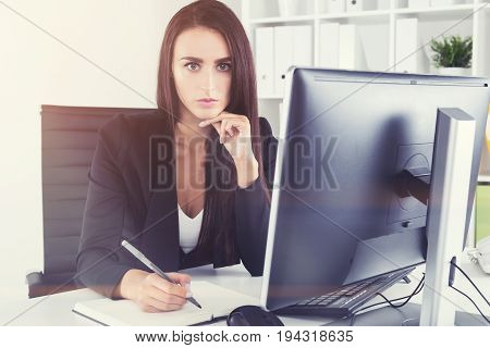 Portrait of a centered and calm self made woman CEO at her workplace in a white office of an international company. Toned image