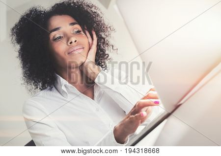 Portrait of a young African American woman sitting at a table and looking at her laptop screen. She is working. Typing with one hand and looking bored. Toned image