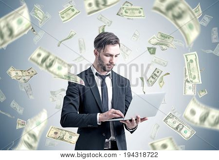 Bearded businessman in a suit is holding his laptop while standing near a gray wall with dollar bills falling around him.