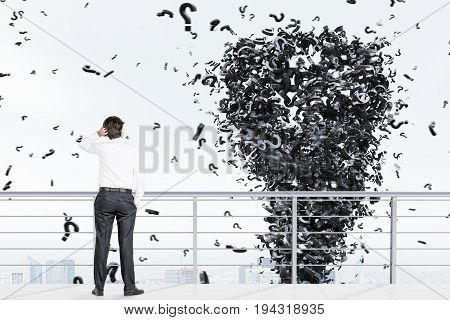 Rear view of a young businessman wearing a white shirt standing on a balcony of a skyscraper looking at a question mark tornado. 3d rendering