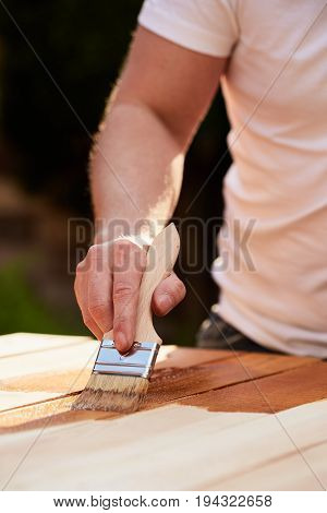 Man With Paintbrush Painting On A Wooden Table