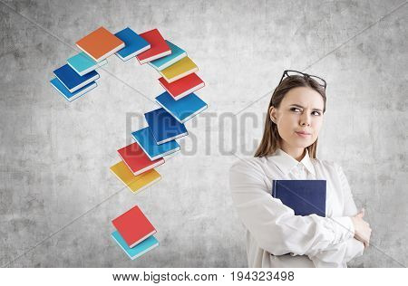 Portrait of a serious young businesswoman in a white shirt hugging a blue book and standing near a concrete wall with a question mark made of book.