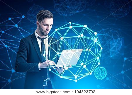 Bearded businessman in a suit is holding his laptop while standing against a blue background with a polygonal orb in the air. Toned image double exposure mock up