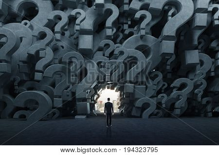 Rear view of a businessman in a black suit standing in an empty room with gray 3d question marks on the walls. There is a way out near him. Concept of an answer search. 3d rendering mock up