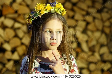 Young Pretty Girl In Flowers Wreath Is Staying Near The Woodpile  In The Village.