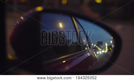 Point of View. Defocused city lights at night in rearview mirrors. Moscow, june, POV
