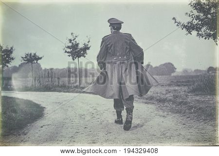 Antique Black And White Photo Of Vintage 1940S Military Officer Walking On Rural Road. Rear View.