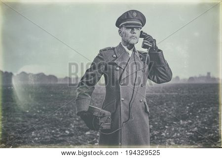 Antique Black And White Photo Of 1940S Military Officer Calling With Field Phone On Farmland.