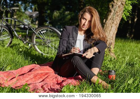 People lifestyle transport and ecology. Portrait of serious young sucessful beautiful Caucasian woman in formal suit having coffee break at park enjoying summer day and making notes in her dairy.