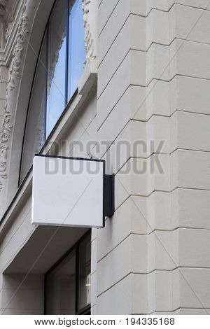 Vertical front view of empty white square signage on a building with classical architecture