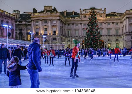 London England UK - December 292016: People enjoying skating at Somerset House at dusk and shows a large Christmas tree against the backdrop of the building.