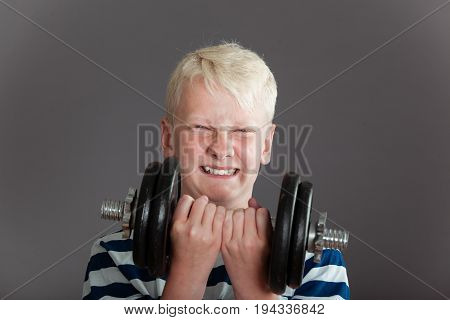 Blond Boy Trying To Lift Heavy Dumbbell