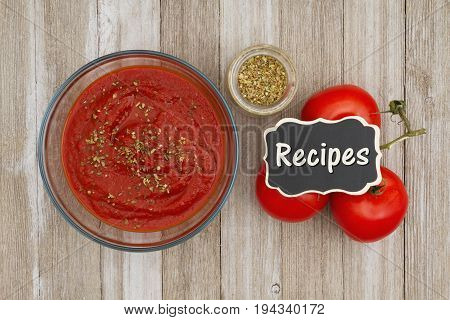 Tomato sauce in clear bowl with oregano spice and red vine ripe tomatoes on weathered wood background with chalkboard with text Recipes