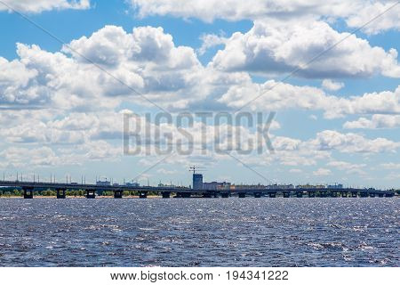 Road bridge across the Volga river between the cities of Saratov and Engels, Russia. Summer river landscape. Blue sky, white clouds.