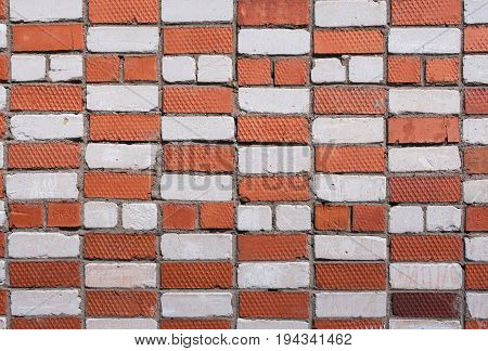 Grange background. Wall with masonry from white and red bricks.