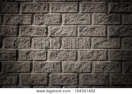 Grunge background. Illuminated gray concrete wall with masonry imitation.