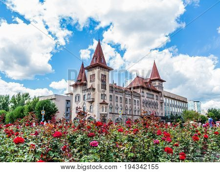 Saratov State Conservatoire. Was opened in 1912. Russia. Blooming roses in the foreground. Clouds on a blue sky.