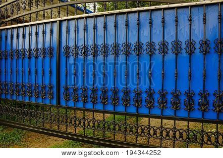 Black blue gates made of plastic and steel forged bars