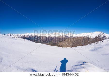 Wide Angle View Of A Ski Resort In The Distance With Elegant Mountain Peaks Arising From The Alpine