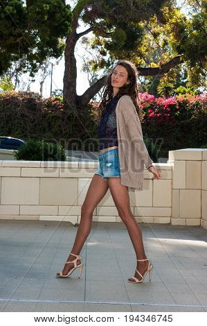 Pretty brunette in tan pantyhose and sweater and open toe heels walking with confidence.
