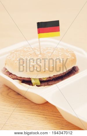 Fresh hamburger with German flag decoration on wooden surface