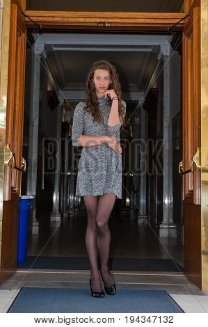 Pretty brunette in black pantyhose, short dress, and pumps looking coy in dark hallway.