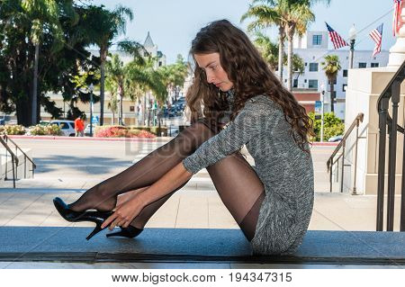 Pretty backlit brunette in black pantyhose, short dress, and pumps seated over Downtown adjusting her shoe.