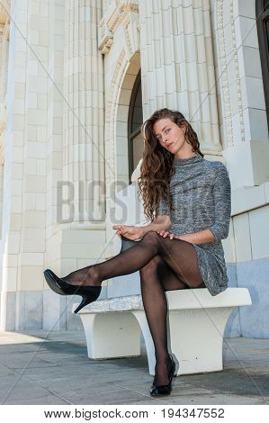 Pretty brunette in black pantyhose, short dress, and pumps stretching nylon away from leg.