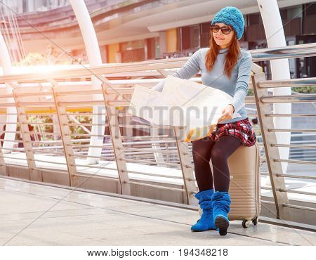 tourists girl asian searching location for travel on paper map with airport background.