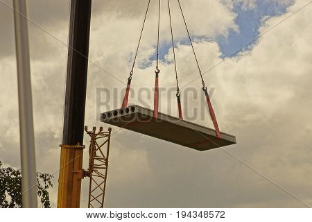 A concrete slab is lifted by a crane on a construction site