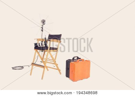 Director's chair and reflector umbrella with suitcases in studio