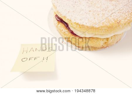 Sponge cake with 'hands off' sign on sticky notepaper