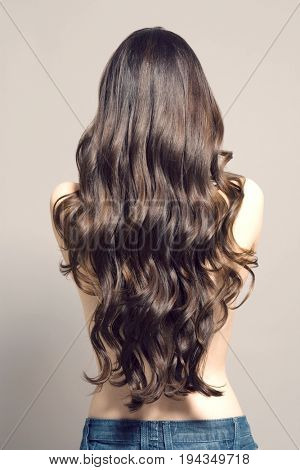 Rear view of a topless woman with long brown wavy hair against gray background