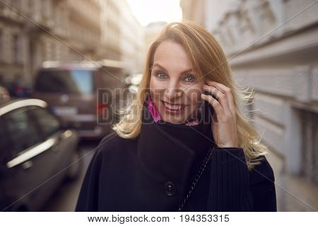 Pretty vivacious woman chatting on a mobile phone as she walks down a busy urban street smiling happily at the camera