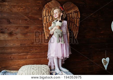 Cute Little Girl In Lovely Dress Posing With A Toy Against Wooden Veneer Wall With Angel Wings On It