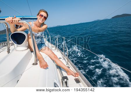 Happy young woman sits on deck of the boat sailing in the tropical sea
