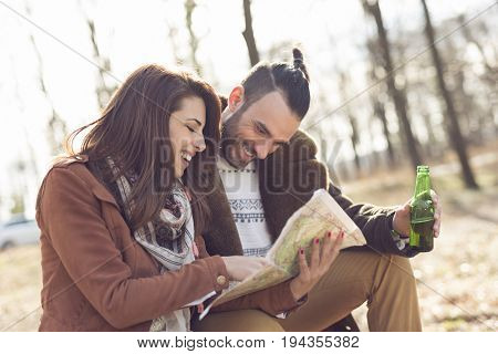 Young couple sitting on a wooden bench by the forest road reading the map and planning the route