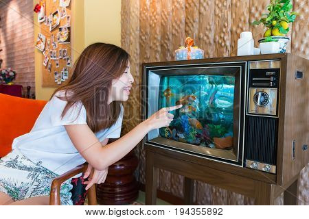 an Asian girl is playing with the goldfish in the tv fish tank strange furniture