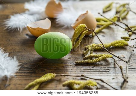 easter eggs and feathers on an old wooden table