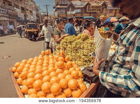 MYSORE, INDIA - FEB 16, 2017: Yellow oranges and grape on marketplace for sell and some customers of busy asian street market on February 16, 2017. Mysore of Karnataka has a population of 900000