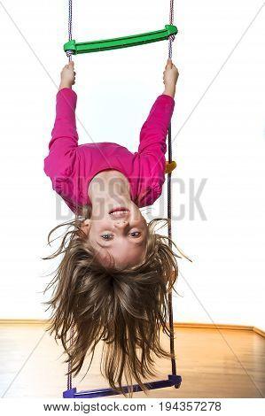 a little girl climbing on a ladder