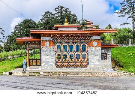 Thimphu Bhutan - September 10 2016: Traditional Bhutanese building near Druk Wangyal Lhakhang. Local Bhutanese man in traditional clothing standing near the door.