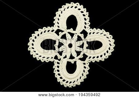 Lace doily on black background. White hand made crocheted coaster on black background. Not isolated.