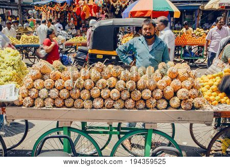 MYSORE, INDIA - FEB 16, 2017: Pineapple trader on big city market and chaos of customers around the busy street on February 16, 2017. Mysore of Karnataka has a population of 900000