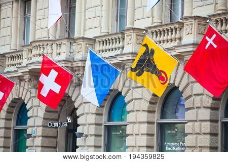 ZURICH - AUGUST 1: Swiss National Day parade on August 1, 2011 in Zurich, Switzerland. Facade of Credit Suisse building decorated with national flag and flags of cantons