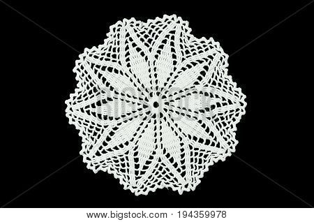 White crocheted coaster on black background. Not isolated. Lace doily.